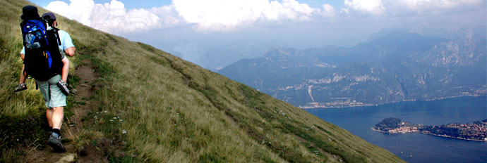 Hiker with child on back in mountains above Griante Lake Como